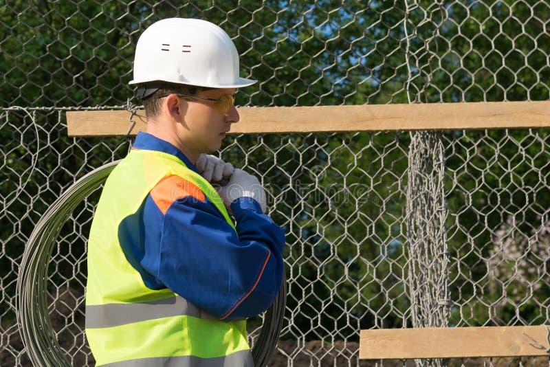 Построитель в прозодеждах носит большое пасмо провода на его плече, конца-вверх взгляда со стороны стоковое изображение rf