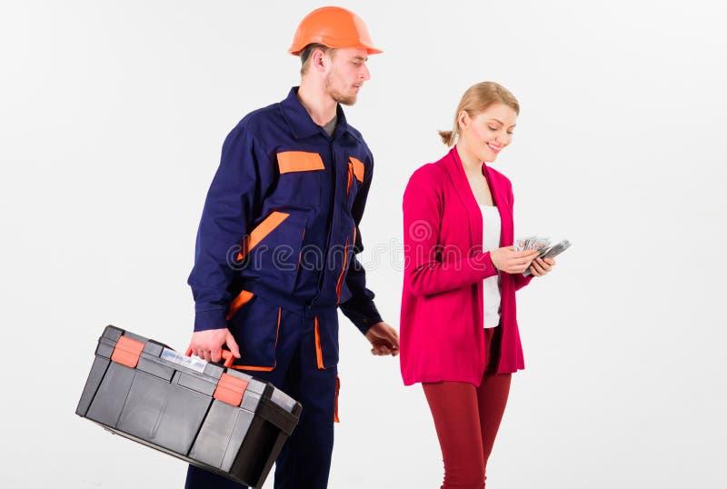 Построитель в шлеме смотрит женщину подсчитывая деньги, стоковые фото