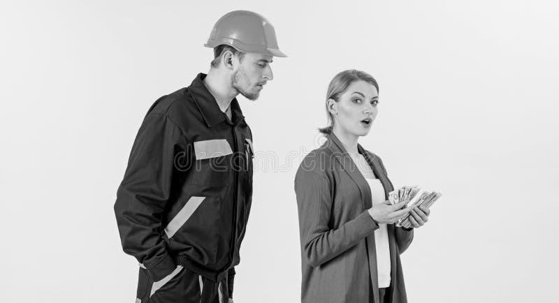 Построитель в шлеме смотрит женщину с занятой стороной стоковые фото