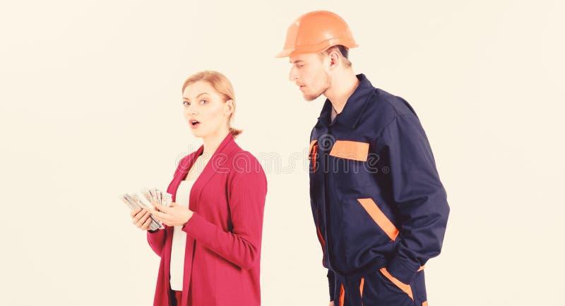 Построитель в шлеме смотрит женщину с занятой стороной стоковые изображения rf