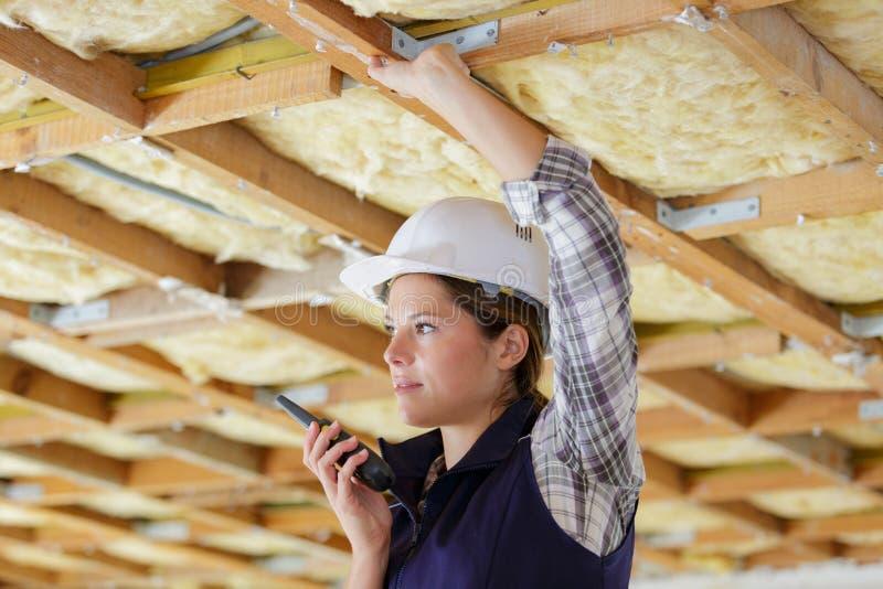 Построитель женщины в защитных одеждах на рации строительной площадки стоковые изображения