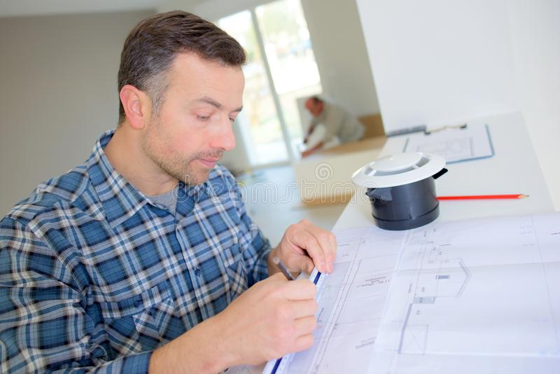 Построитель идя над планами строительства стоковые фото