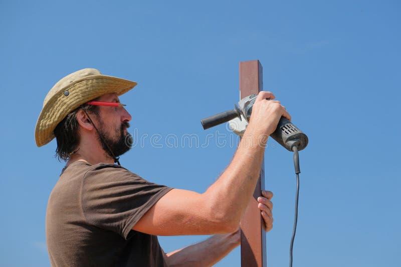 Построитель на точильщике инструментального металла строительной площадки стоковое изображение rf