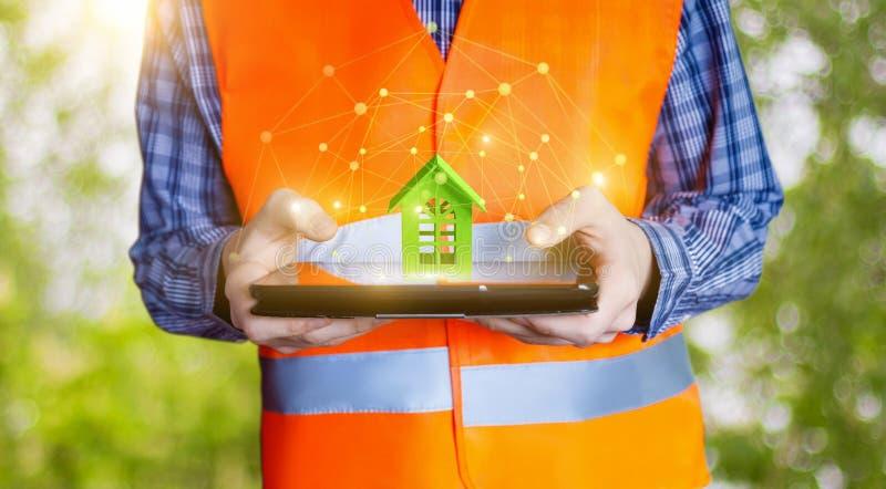 Построитель показывая модельный зеленый дом на таблетке стоковые изображения