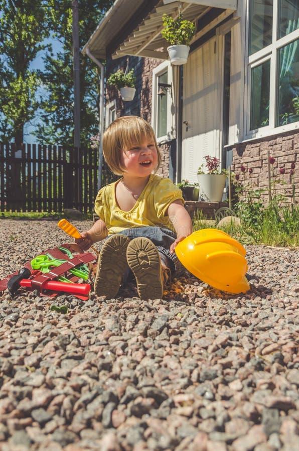 Построитель ребенка с шлемом и комплект инструмента игрушки стоковая фотография rf