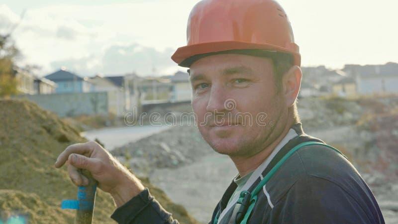 Построитель смотря камеру и усмехаясь на строительной площадке стоковое фото rf