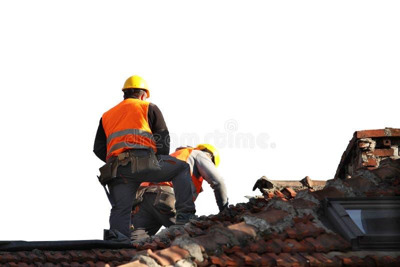 2 построителя в одеждах деятельности исправляя старая крыть черепицей черепицей крыша на здании Строительство на высоте на белом стоковые изображения