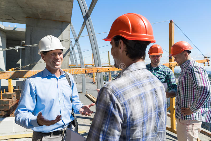 Построители встречая на архитекторе строительной площадки разговаривая с подрядчиком над группой в составе подмастерье стоковые изображения