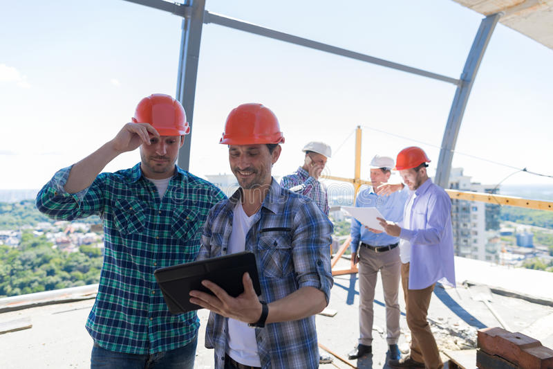 Построители на месте работая с планом строительного проекта на планшете над командой подмастерьев держа светокопию стоковые фотографии rf