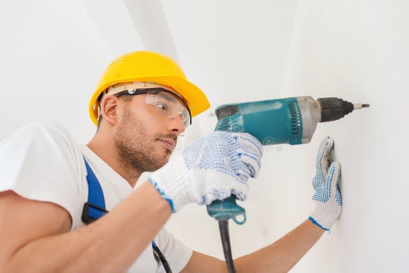 Построитель в защитном шлеме работая с сверлом внутри помещения стоковые фото