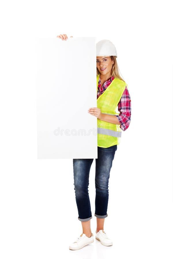 Построитель детенышей усмехаясь женский держа пустое знамя стоковые изображения rf