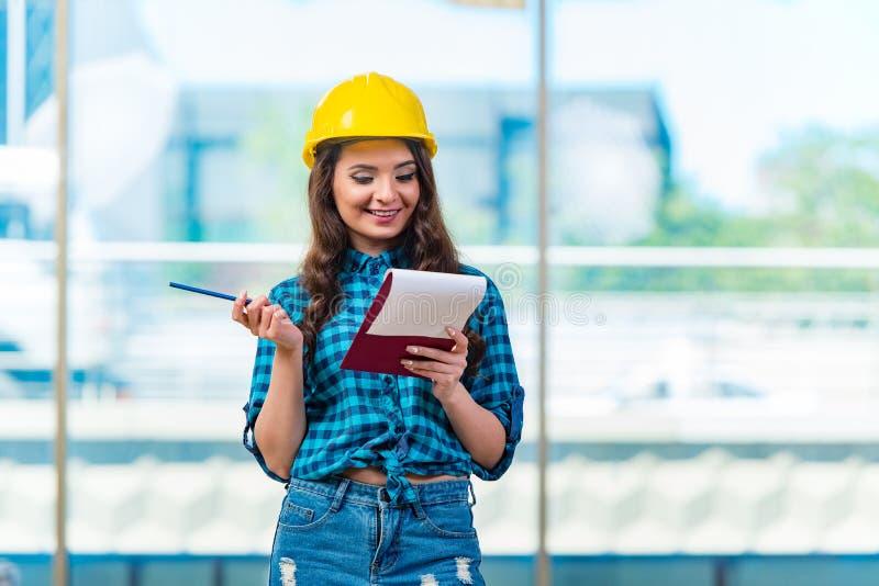 Построитель женщины принимая примечания на строительную площадку стоковые фото