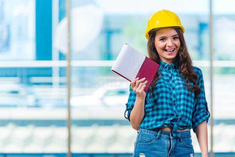 Построитель женщины принимая примечания на строительную площадку стоковое фото rf