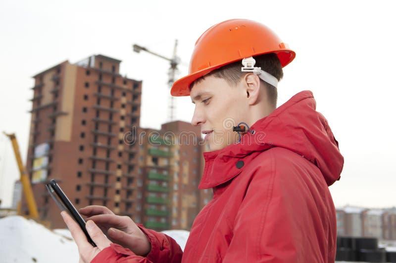 Построитель инженера в шлеме на строительной площадке стоковые изображения