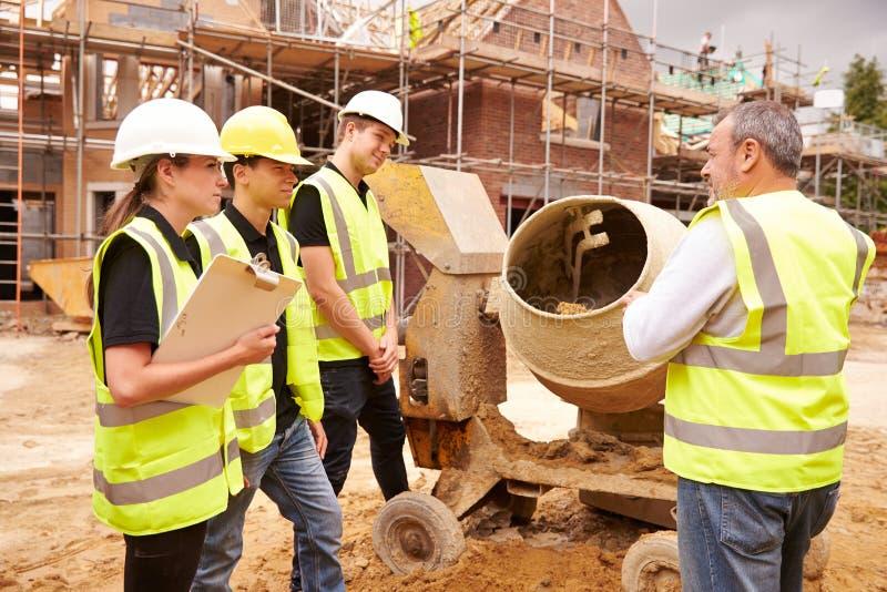 Построитель используя смеситель цемента на строительной площадке с подмастерьями стоковая фотография