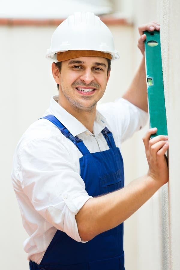 Построитель представляя с уровнем духа стоковое фото