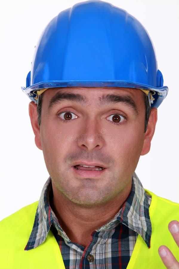 Построитель смотрит confused стоковое фото