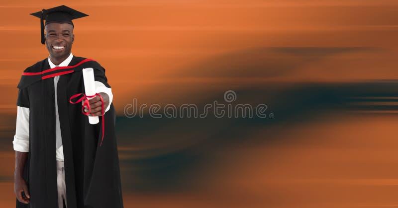 Постдипломный человек усмехаясь против расплывчатой оранжевой абстрактной предпосылки стоковое фото