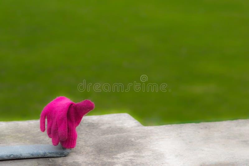 Потерянная розовая перчатка перед зеленым лугом стоковое фото