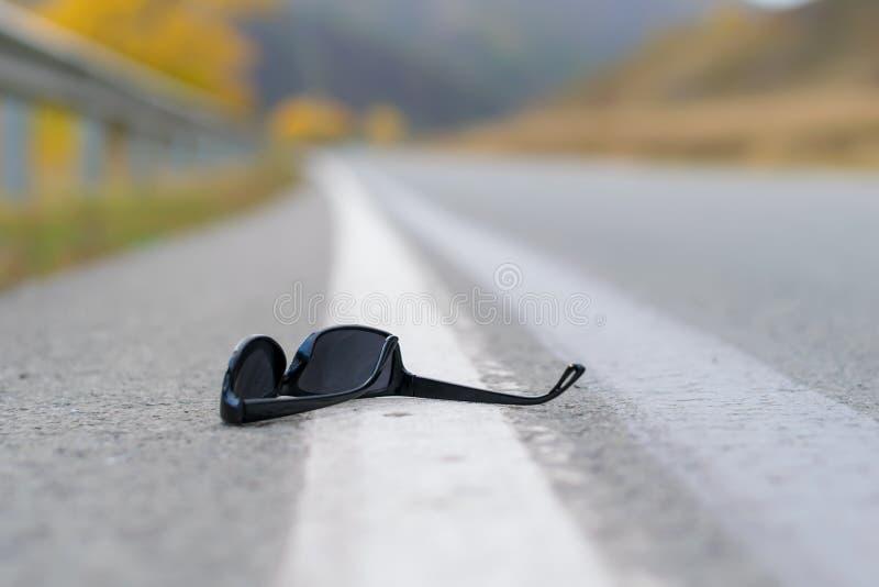 Потерянные солнечные очки лежат на асфальте дороги на следе страны на разделяя прокладке на обочине стоковое фото