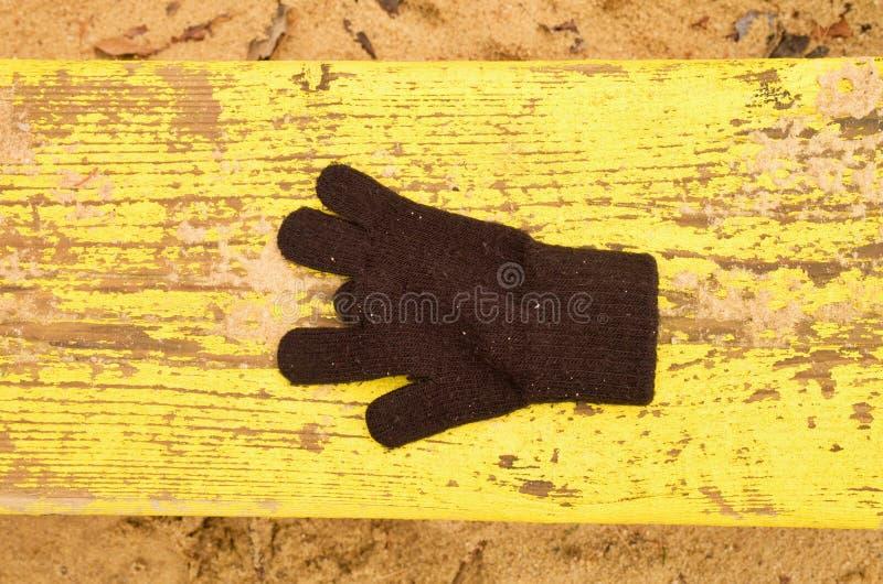 Потерянные шерстяные перчатки на желтом стенде Sandy gren деревянная скамья Ящик с песком с пакостным песком в детском саде стоковое изображение rf