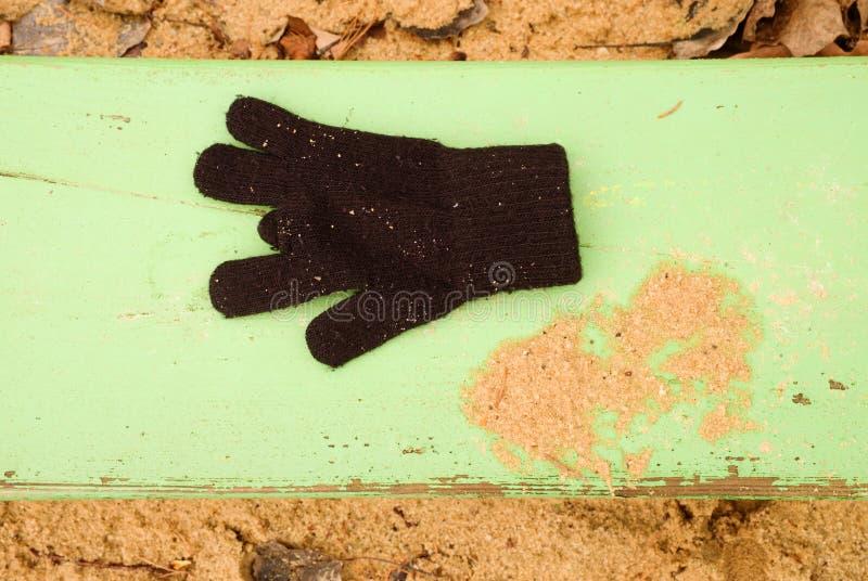 Потерянные шерстяные перчатки на зеленом стенде Sandy gren деревянная скамья Ящик с песком с пакостным песком в детском саде стоковая фотография
