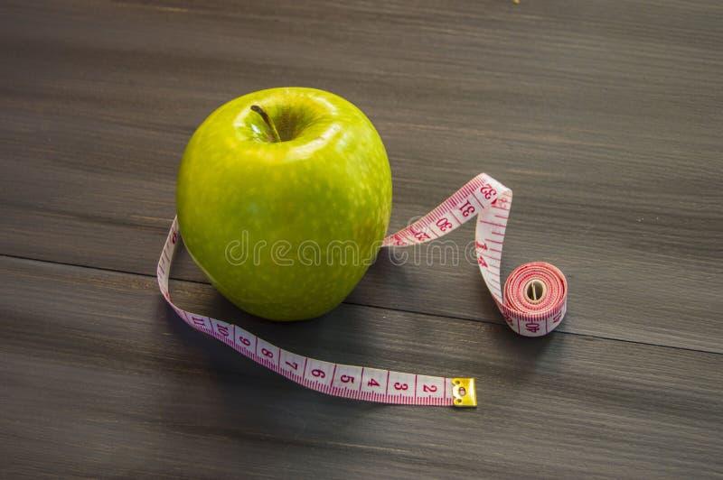Потеря веса, зеленое яблоко и уменьшение, потеря веса с яблоком, преимуществами зеленого яблока, потерей веса, здоровой жизнью стоковая фотография rf