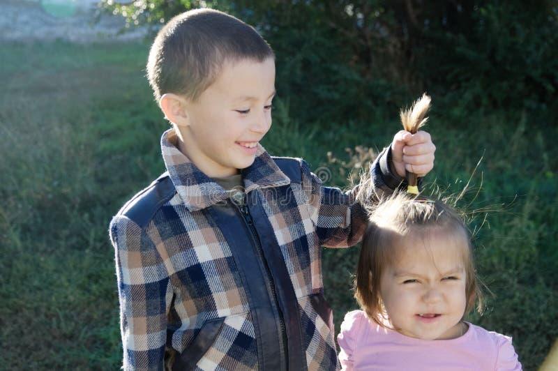 потеха детей имея Портрет мальчика и маленькой девочки Счастливые усмехаясь дети outdoors на солнечном дне Отпрыски приятельства стоковая фотография rf