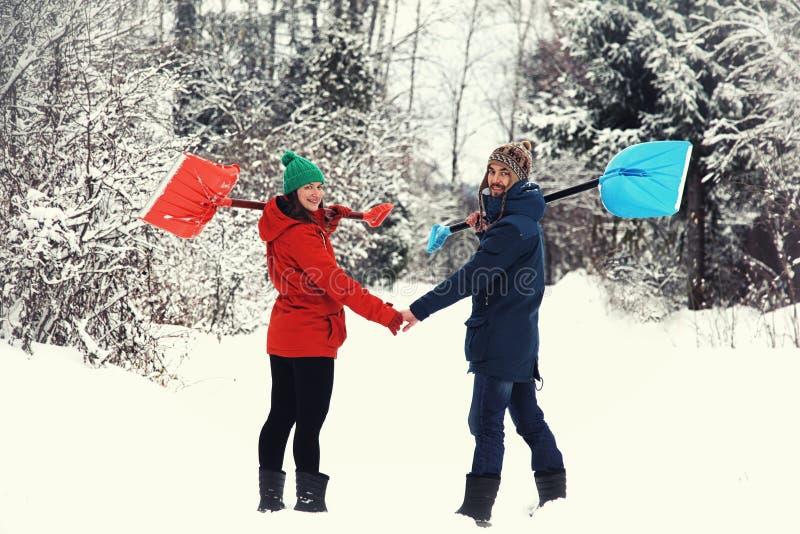 Потеха зимы: счастливые пары с лопаткоулавливателями снега стоковое изображение