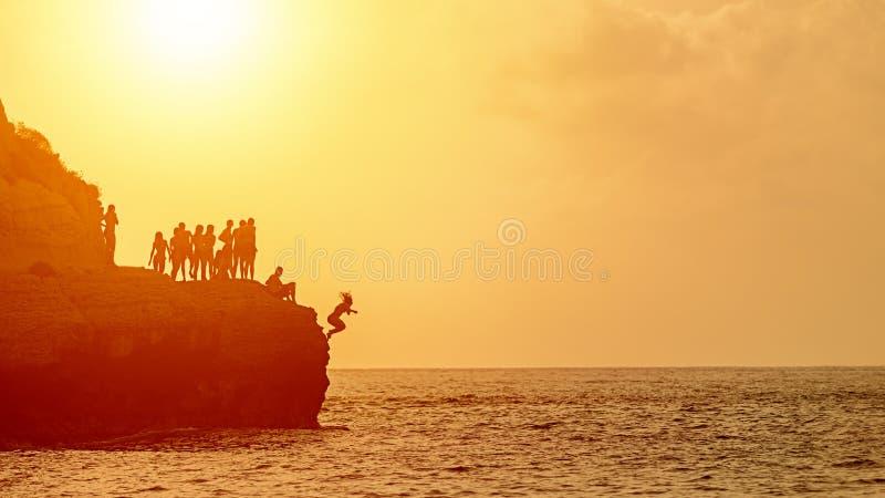 Потеха лета со скалой лучших другов скача в океан, молодые людей силуэта наслаждаясь временем совместно плавая на заходе солнца и стоковые изображения