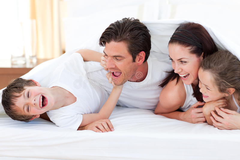 потеха семьи кровати счастливая имеющ лежать стоковая фотография