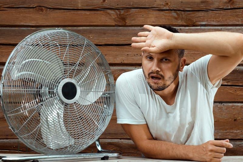 Потный человек перед охлаждая вентилятором, освежая в концепции горячего лета Концепция спасения от жары, горячая стоковая фотография rf