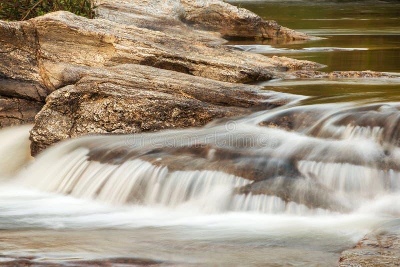 Поток воды бежать над утесами стоковые изображения rf