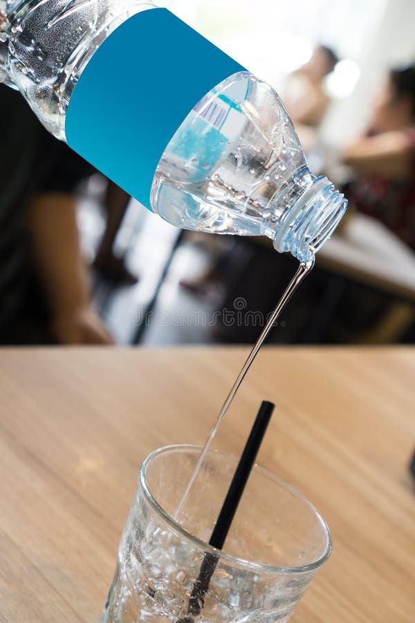 Поток воды политый от бутылки с водой стоковые изображения