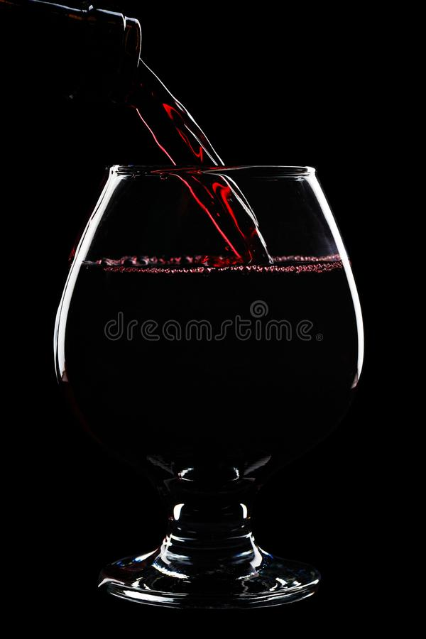 Поток красного вина льет в бокал стоковое фото rf