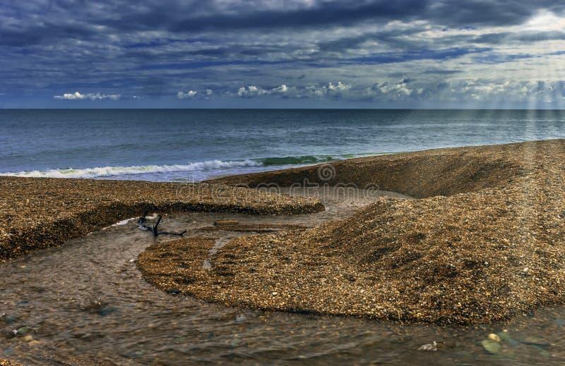 Поток свежей воды идя в море с видимым солнцем излучает - Корнуолл стоковые фотографии rf