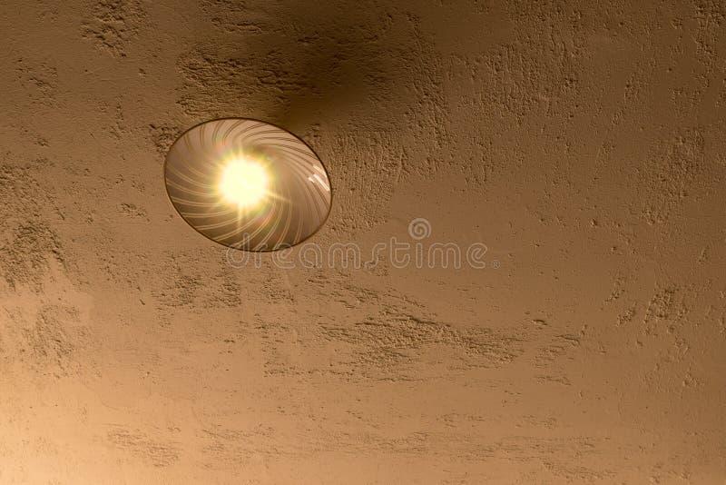 Потолочная лампа на грубом заштукатуренном конкретном потолке стоковое фото rf