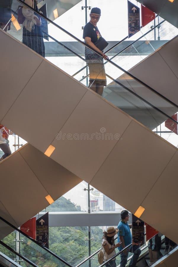 Потребители используют пересеченный эскалатор на пиковой башне на пике Виктории, Гонконге стоковые фотографии rf
