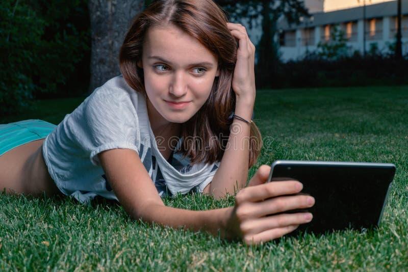 Потребитель планшета маленькой девочки лежа вниз зеленая трава парка и flirting стоковая фотография rf