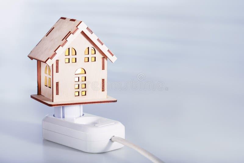 Потребление концепции или поставить электрическую энергию Модельный дом с электрической штепсельной вилкой и гнездом стоковая фотография rf