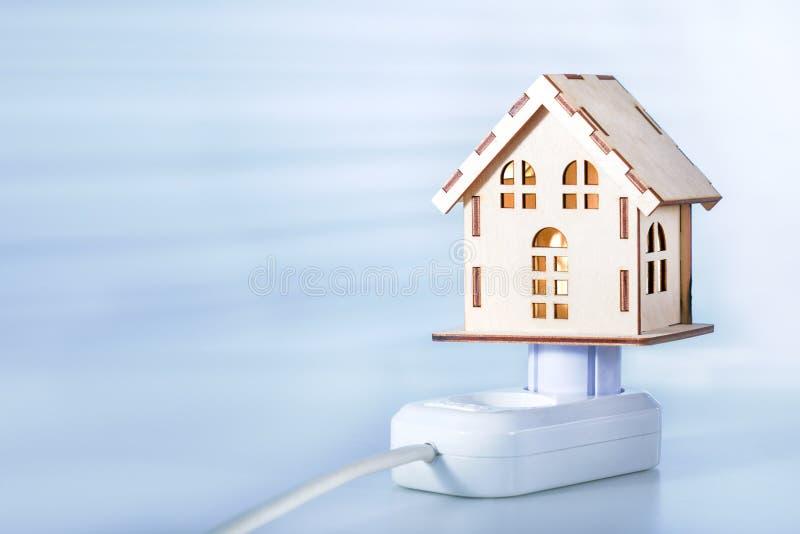 Потребление концепции или поставить электрическую энергию Модельный дом с электрической штепсельной вилкой и гнездом стоковые фото