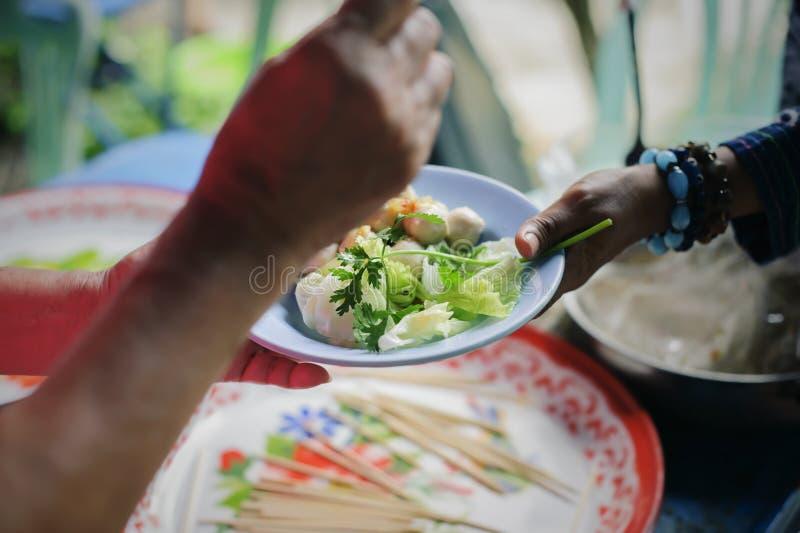 Потребности еды бедных в помощи общества с пожертвованием еды: Бездомные комплектуют вверх еду призрения от дарителей еды в общес стоковое фото rf