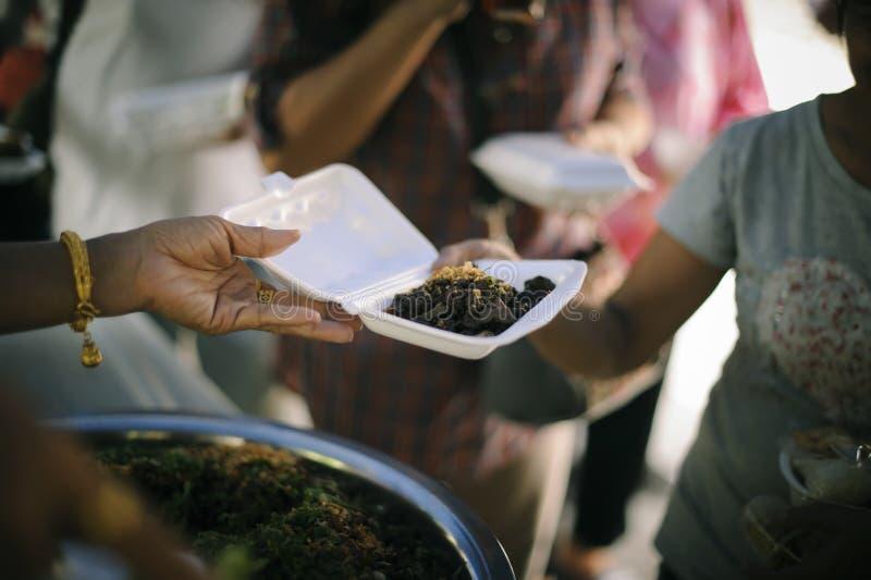 Потребности еды бедных в помощи общества с пожертвованием еды: Бездомные комплектуют вверх еду призрения от дарителей еды в общес стоковые фото