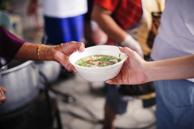 Потребности еды бедных в помощи общества с пожертвованием еды: Бездомные комплектуют вверх еду призрения от дарителей еды в общес стоковое фото