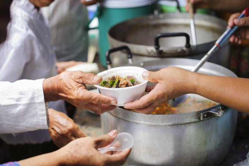 Потребности еды бедных в помощи общества с пожертвованием еды: Бездомные комплектуют вверх еду призрения от дарителей еды в общес стоковая фотография