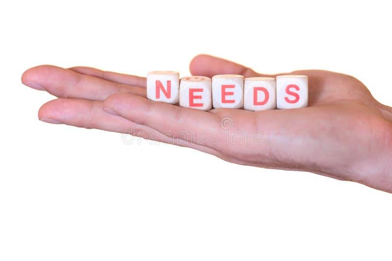 Потребности написанные с деревянной костью на изолированной руке, на белой предпосылке стоковое изображение rf