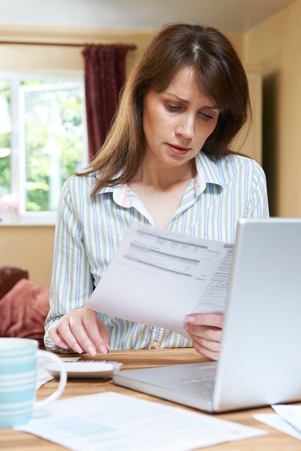 Потревоженная женщина постаретая серединой смотря финансы домочадца стоковые фотографии rf