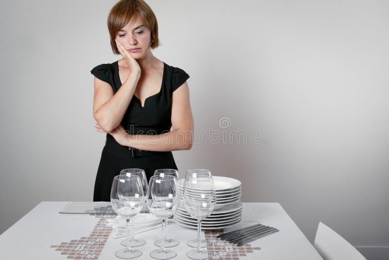 Потревоженная женщина устанавливая таблицу стоковое изображение