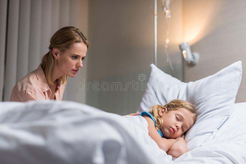потревоженная мать смотря больного ребенк спать на кровати стоковые фото