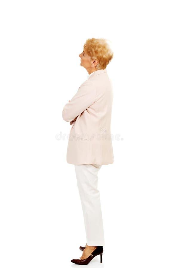 Потревоженная пожилая бизнес-леди при сложенные оружия стоковое изображение